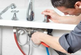 Young handsome plumber repearing bath tub. Service.